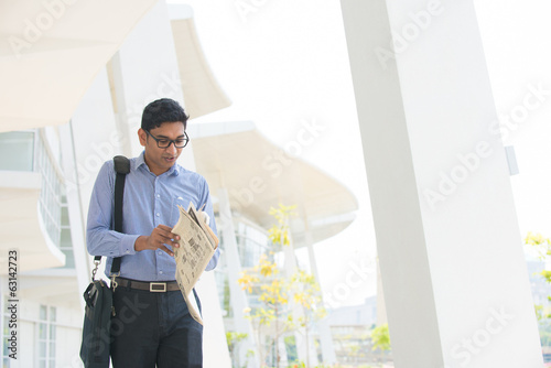 indian business male reading paper and walking