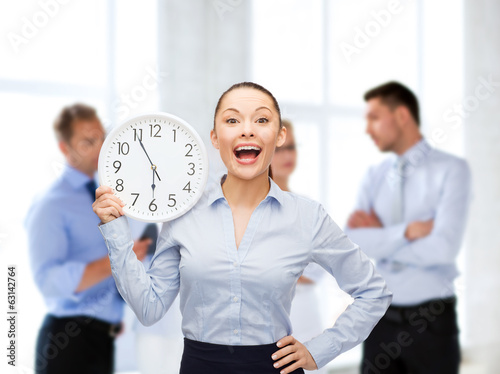 attractive businesswoman with wall clock