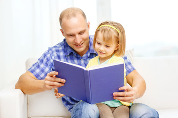 smiling father and daughter with book at home