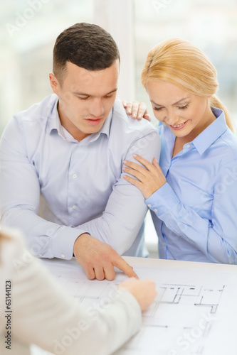 smiling couple looking at blueprint