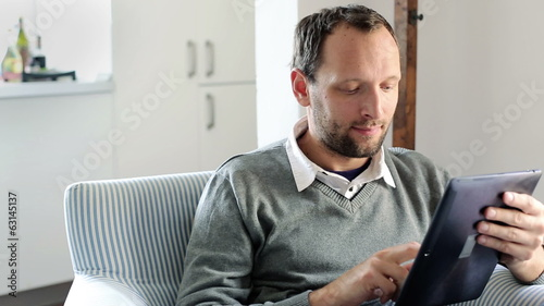 Young handsome man with tablet computer at home