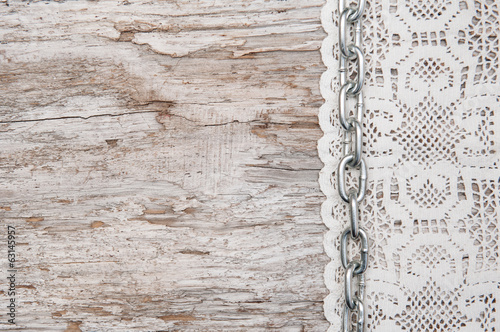 Lace fabric with chain on the old wood