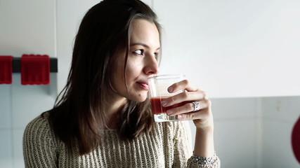 Sad, pensive woman drinking juice in kitchen