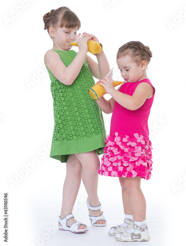 two little girlfriends drink orange juice.