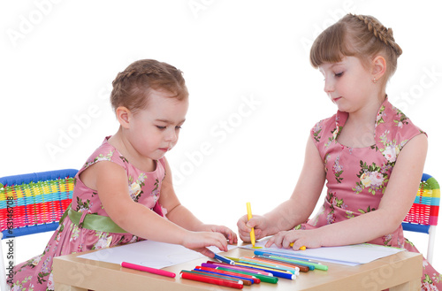 Two little girls in kindergarten paint markers while sitting at