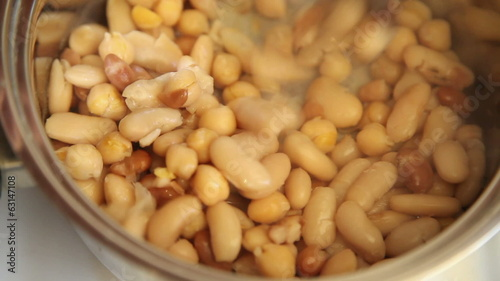 Turning mix of boiling beans in a pot