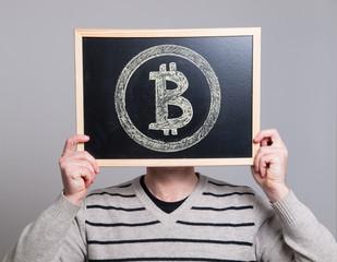 man holding a blackboard with bitcoin symbol