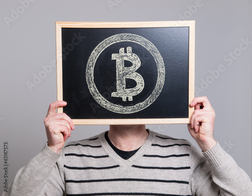 man holding a blackboard with bitcoin symbol