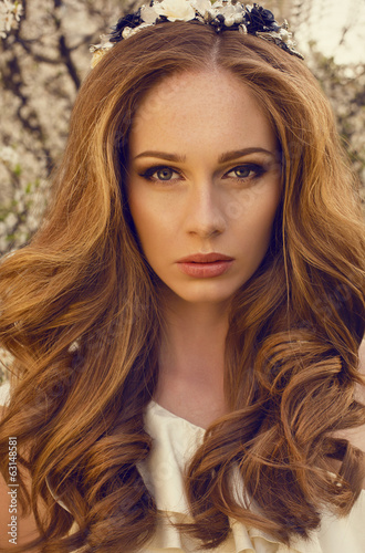 portrait of beautiful woman with red hair in blossom park
