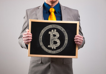 Businessman holding a board with bitcoin symbol