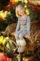 Cute little girl sitting on a cart with hay.