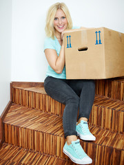 Young woman rests on the stairs with moving box