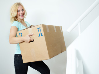 Young woman carries her moving box