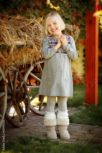 Cute little girl standing near the cart with hay.
