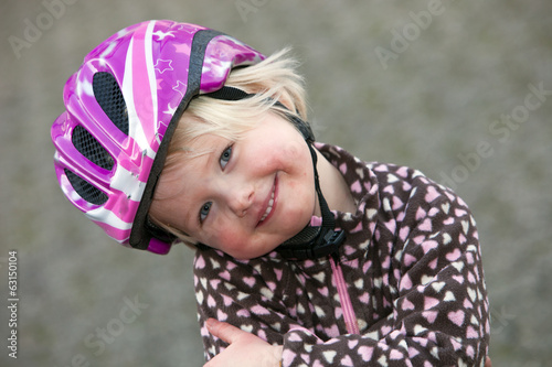 Adorable young girl in a pink safety helmet