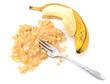 Half-peeled ripe banana with mashed fruit