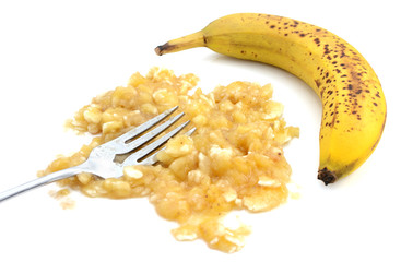 Closeup of mashed banana with fork and an unpeeled fruit