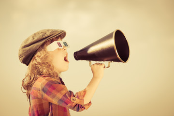 Child shouting through vintage megaphone