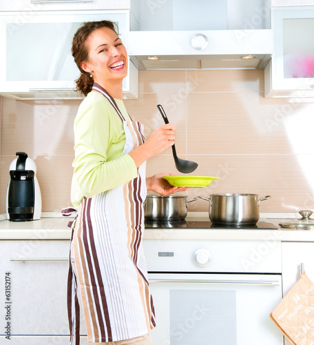 Young woman cooking healthy food at home in the kitchen