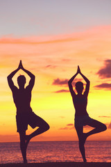 Yoga couple training in sunset in tree pose