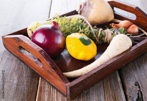 Organic vegetables and herbs on wooden tray