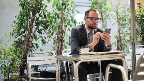 Businessman drinking coffee and using cellphone in restaurant.