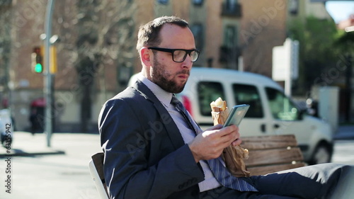 Businessman using cellphone eating baguette on street bench, ste