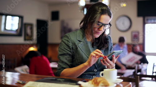Businesswoman in glasses using cellphone in cafe, steadycam shot