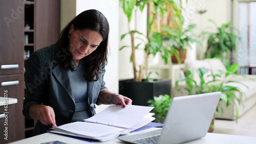 Businesswoman working on laptop checking documents in office, st