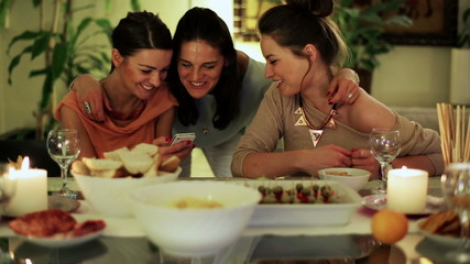 Happy female friends using smartphone at party, front view.