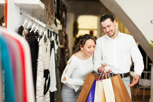 Smiling couple with bags at fasion store