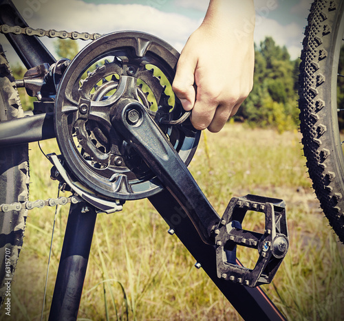 hand with key repairs bike