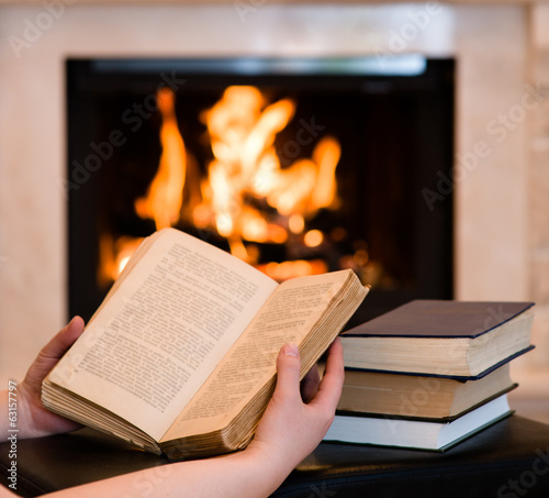 Hands with open book near the fireplace