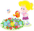 Little girl watering flowers on a flowerbed