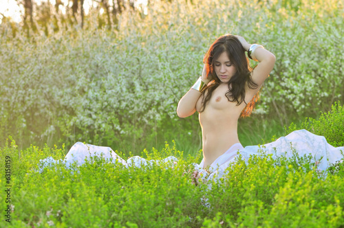 Beautiful girl in a flowered garden topless