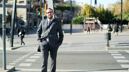 Businessman crossing street and smiling to camera