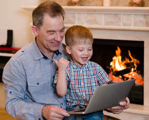 Boy and his grandfather using a notebook. looking at computer