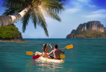 Man and girl kayaking next to a tropical island