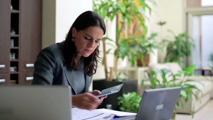 Businesswoman working on cellphone and laptop in office, steadyc