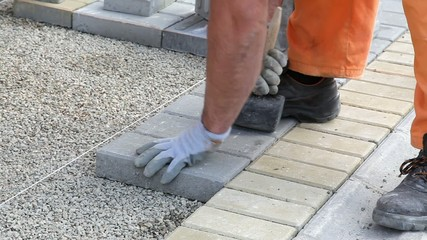 Construction site, worker install concrete brick pavement