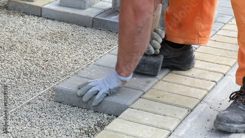 Construction site, worker install concrete brick pavement