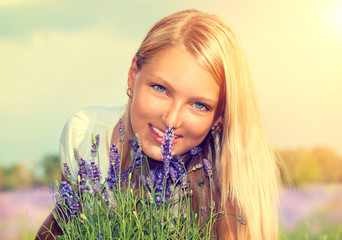 Beautiful Girl with Flowers in Lavender Field