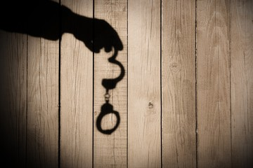 Male Hand with Handcuffs on Natural Wood Background, XXXL.