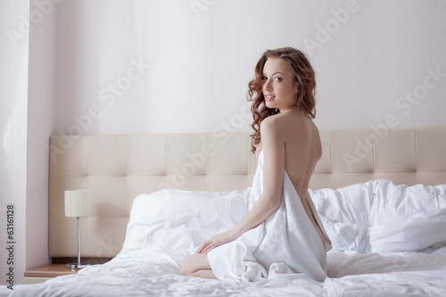 Smiling brunette posing in towel on hotel bed