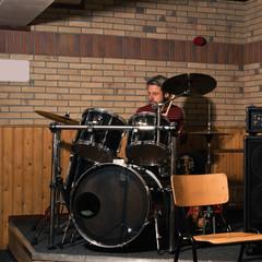 Energetic rock drummer in action. Long blonde hair. Jam session.