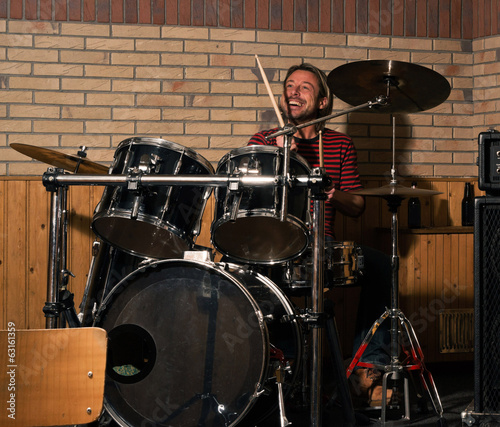 Energetic rock drummer in action. Long blonde hair. Jam session.