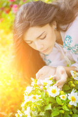 Young girl smelling flowers in garden with the sunshine.