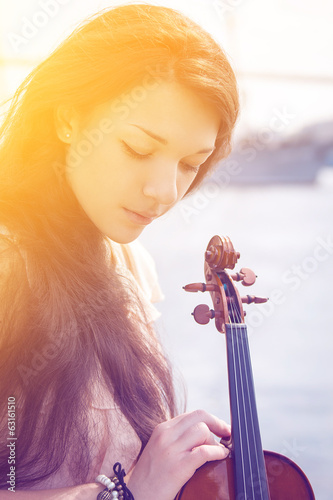 Girl with violin in the sunshine. Color toned image.