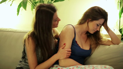 Women consolation on sofa in room at night