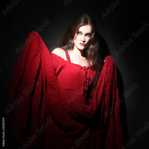 Woman in red dress in darkness. Lady in red